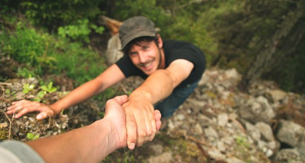 Hand helping a climber man to raise the top