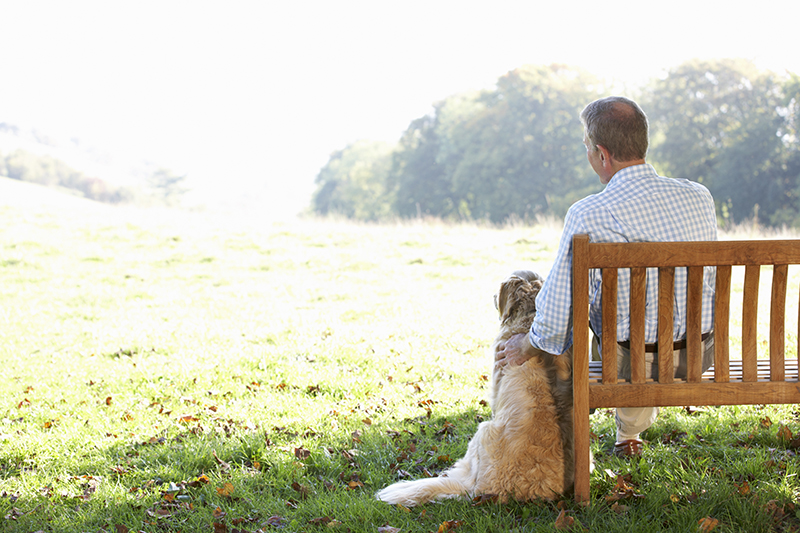 Senior man sitting outdoors with dog